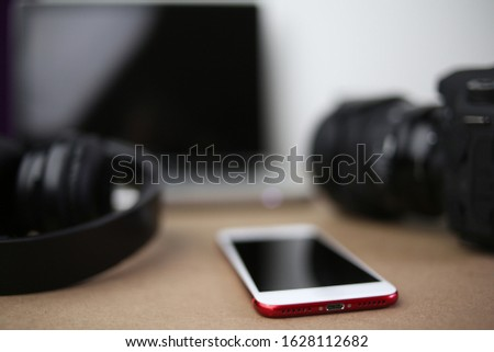 audiovisual production office with camera headphones mobile phone laptop computer photographic and audio equipment