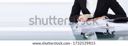 Auditor Doing Financial Audit And Tax Fraud Inspection Using Magnifying Glass Foto stock ©