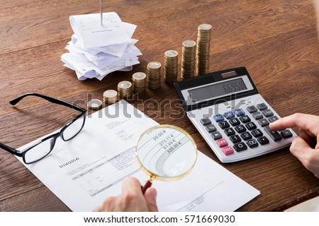 Auditor Hand Checking Invoice Using Magnifying Grass. Tax Fraud Investigation Concept Foto stock ©