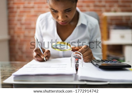 Auditor Investigating Business Fraud Using Magnifying Glass In Office Foto stock ©