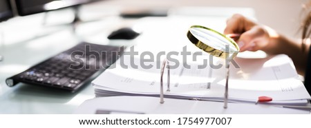 Auditor Investigating Corporate Fraud Using Magnifying Glass ストックフォト ©