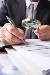 Auditor Using Magnifying Glass For Audit And Fraud Investigation