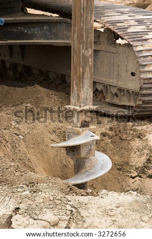 Auger at a construction site digging a hole for a building.