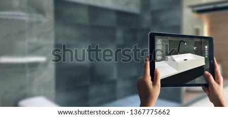 Augmented Reality bathroom planning. Sanitary ware. Hand holding digital tablet in real home background, AR application. A new way to experience products. Copy space.