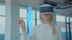 Augmented Reality. Close-up of a Female Doctor Looking: Medical Charts, 3D Hologram (DNA hologram, Pulmonary System, Muscular System, COVID-19) Wearing VR Glasses and Headsets. Future Medicine. VR