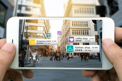 Augmented reality marketing concept. Hand holding smart phone use AR application to check relevant information about the spaces around customer. City and flare light background