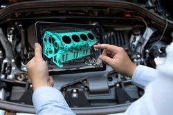 Augmented reality technology and engineering marketing concept. Hand holding tablet with AR service application to rotate 3d rendering of energy block 360 degrees with blur car engine room background