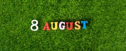 August 8. Image of wooden colored letters and numbers on August 8 against the background of a green lawn, World Cat Day. A summer day. Empty space for the text.