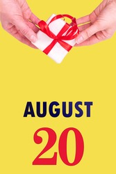 August 20th. Festive Vertical Calendar With Hands Holding White Gift Box With Red Ribbon And Calendar Date 20 August On Illuminating Yellow Background.Summer month, day of the year concept.