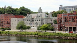 Augusta, ME, USA - July 26, 2020: The Olde Federal Building, landmark edifice, historic downtown waterfront, view across the Kennebec River