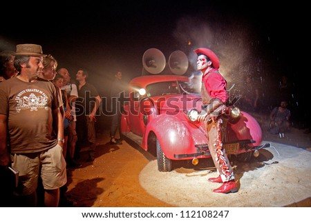 AURILLAC, FRANCE - AUGUST 22: a cowboy arrives in a red car under a big top as part of the Aurillac International Street Theater Festival, Company Off ,on august 22, 2012, in Aurillac,France.