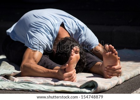 AURILLAC, FRANCE - AUGUST 22:  a dancer is stretching as part of the Aurillac International Street Theater Festival, Company Monsieur Linea,on august 22, 2013, in Aurillac,France
