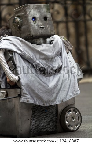 AURILLAC, FRANCE - AUGUST 24: a grey robot in the street as part of the Aurillac International Street Theater Festival, show Robot Nozomi, on august 24, 2012, in Aurillac,France. - stock photo