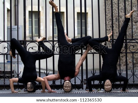 AURILLAC, FRANCE - AUGUST 23: actors upside down in the street as part of the Aurillac International Street Theater Festival, show La diagonale du Fou, on august 23, 2012, in Aurillac,France.