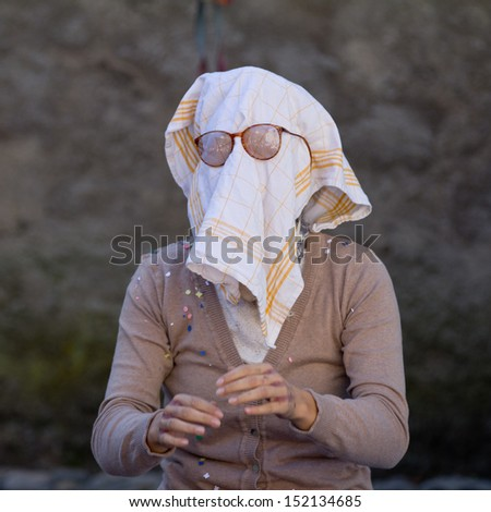 AURILLAC, FRANCE - AUGUST 21:an old woman wears a dish towel on the face as part of the Aurillac International Street Theater Festival, Company L'arbre a  vache ,on august 21, 2013, in Aurillac,France.