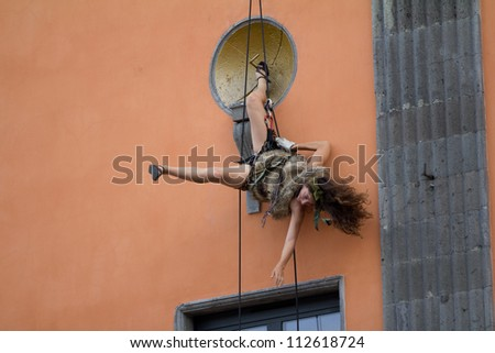 AURILLAC, FRANCE - AUGUST 22: an unidentified artist goes down along a facade as part of  the Aurillac International Street Theater Festival on august 22, 2012, in Aurillac,France.