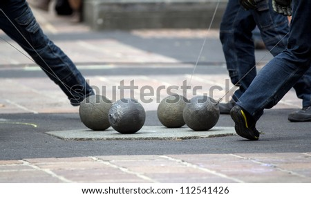 AURILLAC, FRANCE - AUGUST 24: show with four heavy balls on the ground as part of the Aurillac International Street Theater Festival, show New town, on august 24, 2012, in Aurillac,France.