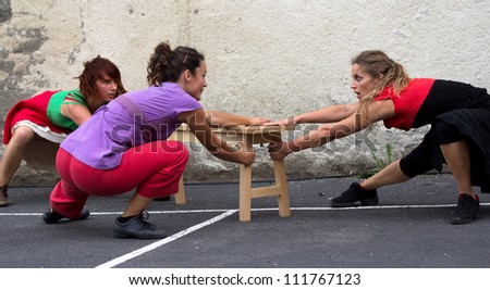 AURILLAC, FRANCE - AUGUST 24 : three dancers are quarelling around a bench, Aurillac International Street Theater Festival, Company D'Akipaya Danza , on august 24, 2012, in Aurillac,France.