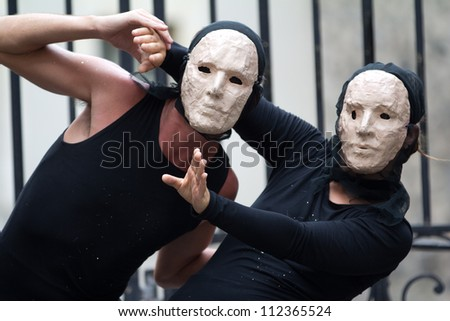 AURILLAC, FRANCE - AUGUST 23: two actors wearing a white mask as part of the Aurillac International Street Theater Festival, show La diagonale du Fou, on august 23, 2012, in Aurillac,France.