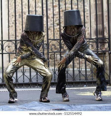 AURILLAC, FRANCE - AUGUST 23: Two dancers, with a bucket on the head, move as Michael Jackson, Aurillac International Street Theater Festival, show Vachement, on august 23, 2012, in Aurillac,France.