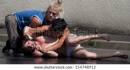 AURILLAC, FRANCE - AUGUST 22: two semi-naked men fight on the ground as part of the Aurillac International Street Theater Festival, Company Monsieur Linea,on august 22, 2013, in Aurillac,France