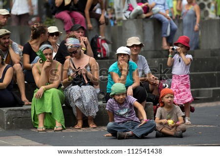 AURILLAC, FRANCE - AUGUST 24:unidentified spectators looking at a public entertainment  as part of the Aurillac International Street Theater Festival, show New town, on august 24, 2012, in Aurillac,France.
