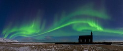 Aurora borealis above the church. Jokulsarlon glacier lagoon, Iceland. Green northern lights. Starry sky with polar lights. Night winter landscape with aurora, sea with sky reflection in water.