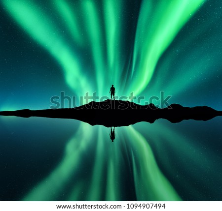 Aurora borealis and silhouette of standing man. Lofoten islands, Norway. Aurora and happy man. Stars and green polar lights. Night landscape with aurora, man, lake, sky reflection in water. Travel