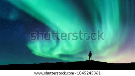 Aurora borealis and silhouette of standing man. Lofoten islands, Norway. Aurora and happy man. Sky with stars and green polar lights. Night landscape with aurora and people. Concept. Nature background #1045245361