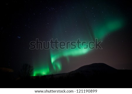 Aurora Borealis in arctic skies behind mountains in Norway