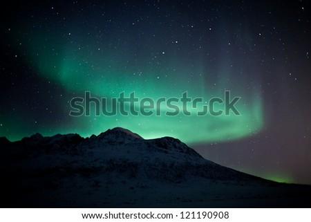 Aurora Borealis in arctic skies behind mountains in Norway