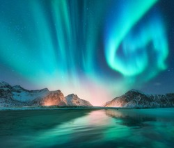Aurora borealis in Lofoten islands, Norway. Aurora. Green northern lights. Starry sky with polar lights. Night winter landscape with aurora, sea with sky reflection, stones, beach and snowy mountains