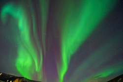Aurora borealis in the night sky. The light colors are green, yellow, and red. Photographed in Alaska, the USA on March 17, 2016
