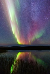 Aurora borealis on Iceland with lake reflection