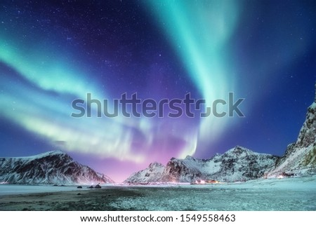Aurora borealis on the Lofoten islands, Norway. Green northern lights above mountains. Night winter landscape with aurora. Natural background in the Norway Stock photo ©