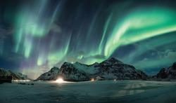 Aurora borealis or Northern lights over snow mountain on coastline in Flakstad, Lofoten islands