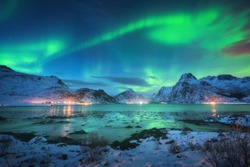 Aurora borealis over the sea coast, snowy mountains and city lights at night. Northern lights in Lofoten islands, Norway. Starry sky with polar lights. Winter landscape with aurora reflected in water