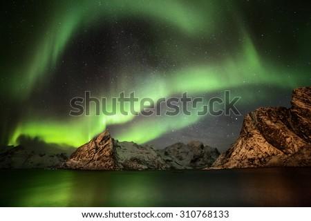 Aurora borealis (Polar lights) over the Lilandstinden mountain peak - Reinefjorden, Lofoten islands, Norway (panorama) - Shutterstock ID 310768133