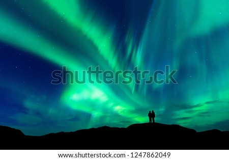 Aurora borealis with silhouette love romantic couple on the mountain.Honeymoon travel concept #1247862049