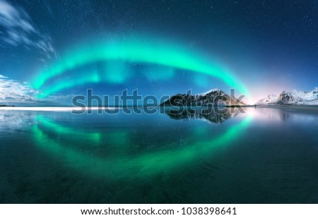 Aurora. Northern lights in Lofoten islands, Norway. Starry blue sky with polar lights. Night winter landscape with aurora, sea with sky reflection, beach, mountains, city lights. Green aurora borealis #1038398641
