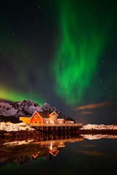 Aurora over a red house reflecting in the bay