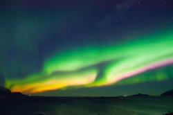 Aurora with muliple colors in green, orange and pink. Burst in the middle of Norwegian sea.