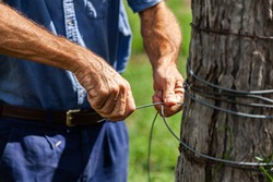Aussie farmer repairing fence wires after flood damage on Australian farm