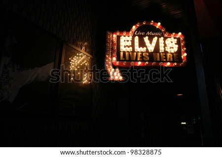 """AUSTIN, TEXAS - MAR 10: SXSW 2012 on March 10, 2012 in Austin, Texas.  """"Elvis LIves Here"""" Sign is part of the tribute to Elvis Presley by Beale Street Tavern located in the historic 6th Street of downtown Austin where SXSW takes place."""