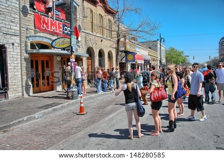 AUSTIN, TX - MAR 14: Tourists enjoy SXSW festival in city streets, March 14 2008 in Austin. SXSW began in 1987, and has continued to grow in size every year.