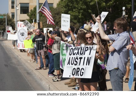 AUSTIN, TX - OCTOBER 15:  An unidentified woman greets traffic during the 'Occupy Austin' general assembly in preparation for the march to the Texas State Capitol on October 15, 2011 in Austin.