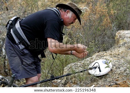 AUSTRALIA - APRIL 24: The gold miner observes his discovery to see if what he found is gold or just iron, April 24, 2007