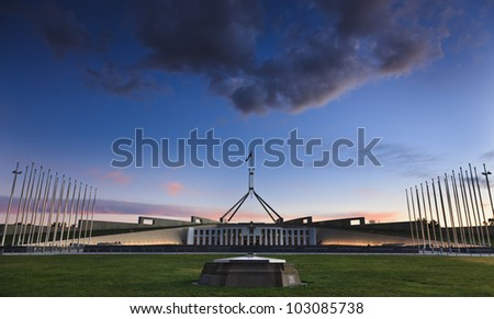 Australia Canberra acting as capital territory ACT Parliament building at sunset with illuminated facade and flagpoles