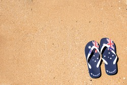Australia Day and travel destination background: patriotic Aussie thongs featuring Australian flag on the beautiful on the sand