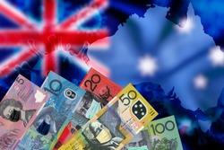 Australia dollar money bill with face mask on money notes over Australia flag and map blurred background, COVID-19 coronavirus in Australia.